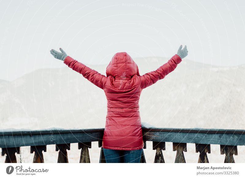 Frau steht mit erhobenen Händen mit Blick auf die Berge Lifestyle Ferien & Urlaub & Reisen Tourismus Ausflug Abenteuer Freiheit Winter Winterurlaub