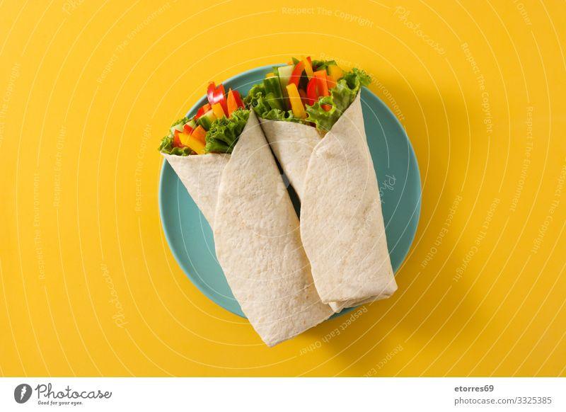 Pflanzliche Tortilla-Wraps isoliert auf gelbem Hintergrund. Ansicht von oben Gemüse umhüllen Brötchen Fladenbrot Lebensmittel Gesunde Ernährung Foodfotografie