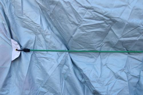 kurz angebunden | wörtlich genommen - hellblaue faltige Plastikplane wird mit einem Gummiband festgehalten Plane festhalten Falten Schutz Farbfoto
