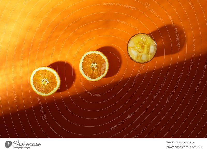 Kaltes Orangensaftglas und im Sonnenlicht halbierte Orangen Frucht Frühstück Getränk Erfrischungsgetränk Glas obere Ansicht Zitrusfrüchte farbenfroh halbieren