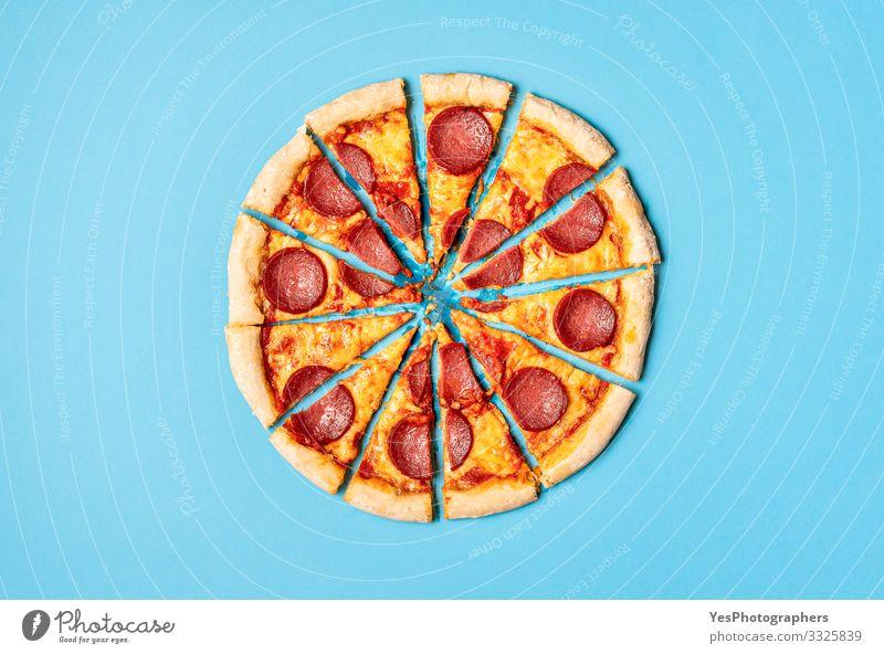 Geschnittene Pizza-Peperoni auf blauem Hintergrund. Pizza-Salamischeiben Lebensmittel Teigwaren Backwaren Abendessen Italienische Küche lecker gold Tradition