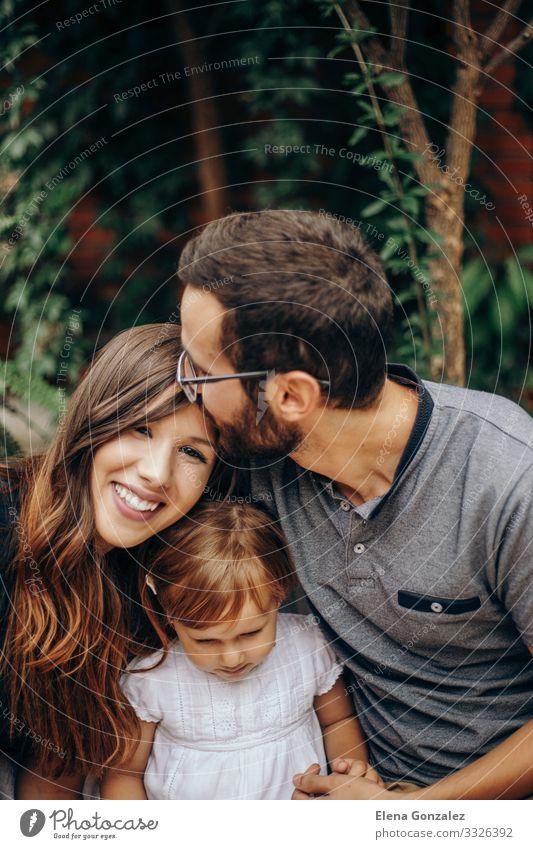 Kleines blondes Mädchen, das zwischen Vater und Mutter sitzt. Vater küsst Mutter auf den Kopf. Die Tochter genießt mit ihren jungen Eltern im Garten. Liebe und Familienkonzept.
