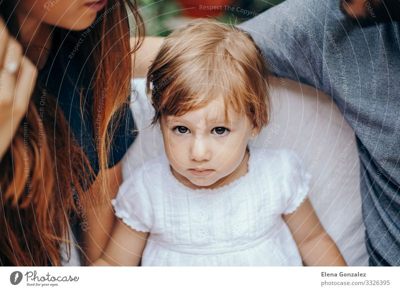 Ernsthaftes kleines blondes Mädchen, das zwischen Mon und Dad sitzt. Gesicht Erholung Kind Baby Kleinkind Eltern Erwachsene Kindheit Kleid sitzen niedlich