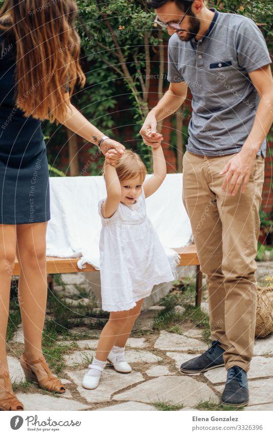 Kleines blondes Mädchen spielt und hält die Hand ihrer jungen Eltern. Spielen Freiheit Garten Hochzeit Kindererziehung Baby Mann Erwachsene Mutter Vater