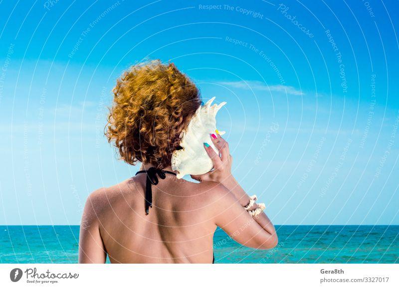 junge Frau mit roten Haaren mit einer großen Muschel Maniküre Ferien & Urlaub & Reisen Sommer Strand Meer Junge Frau Jugendliche Erwachsene Finger Natur Wolken