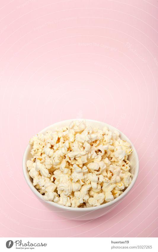 Popcorn auf farbigen Hintergründen Lebensmittel Picknick Fastfood Schalen & Schüsseln Entertainment Kino frisch lecker rosa weiß Farbe Popkorn Snack Mais salzig