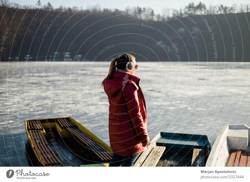 Junge Frau steht am gefrorenen See Freiheit Winter Mensch feminin Jugendliche Erwachsene Leben 1 30-45 Jahre Natur Wasser Eis Frost Seeufer Fluss Fischerboot