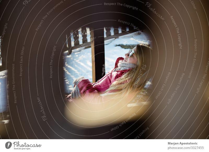 Frau, die an einem Wintertag draußen auf dem Stuhl sitzt Lifestyle Freude Ferien & Urlaub & Reisen Tourismus Winterurlaub Berge u. Gebirge Mensch feminin