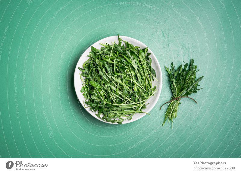 Rucola-Salat und Rucola-Bündel auf grünem Tisch. Frische Kräuter Gemüse Salatbeilage Vegetarische Ernährung Diät Gesunde Ernährung Garten Gartenarbeit Pflanze