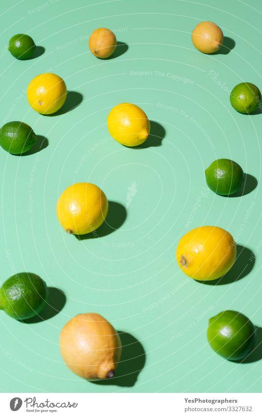 Zitronen- und Limettenfrüchte auf grünem Hintergrund. Sommerfrüchte Lebensmittel Frucht Frühstück Schönes Wetter frisch Aquaminthe heiter Zitrusfrüchte