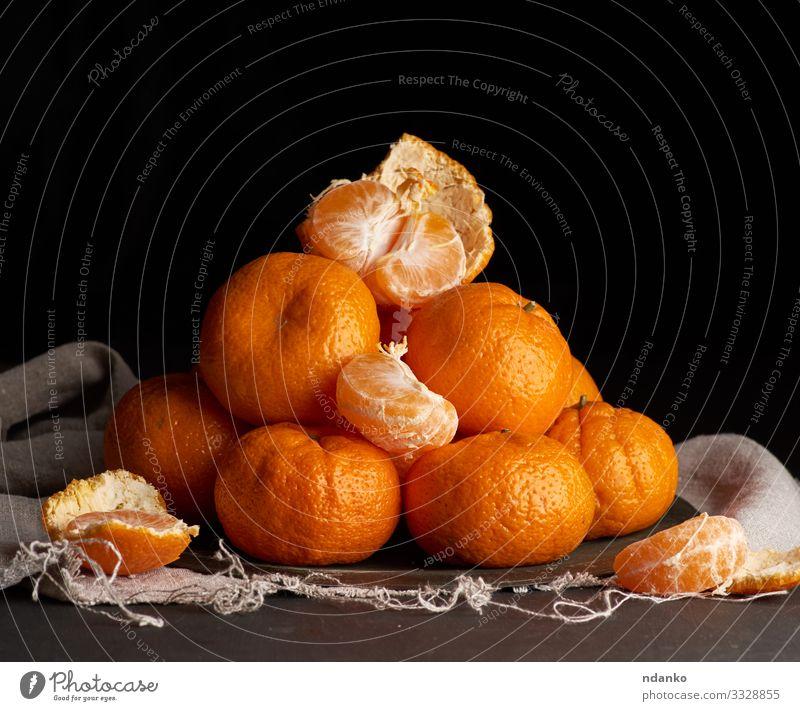 ungeschälte runde reife orangefarbene Mandarine Frucht Dessert Ernährung Vegetarische Ernährung Saft Teller Tisch Holz dunkel frisch natürlich saftig gelb grau