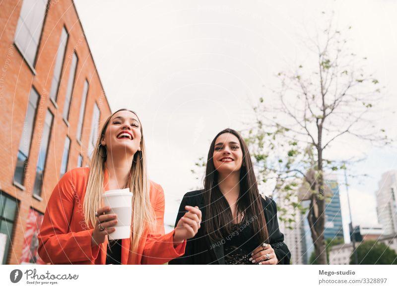 Zwei junge Freunde, die zusammen im Freien spazieren gehen. Lifestyle Stil Freude Glück Leben Ferien & Urlaub & Reisen sprechen Mensch feminin Frau Erwachsene