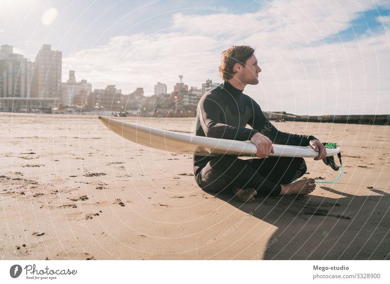 Surfer, der mit einem Surfbrett am Sandstrand sitzt. Lifestyle Glück Erholung Freizeit & Hobby Abenteuer Strand Meer Wellen Sport Wassersport Mensch maskulin