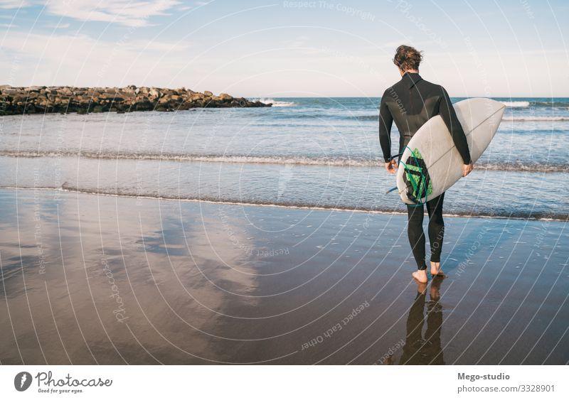 Surfer, der mit seinem Surfbrett ins Wasser geht. Lifestyle Freude Erholung Abenteuer Strand Meer Wellen Sport Wassersport Mensch maskulin Mann Erwachsene 1