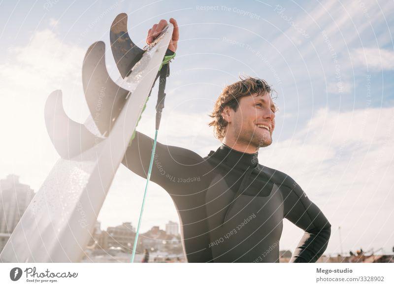 Surfer, der mit einem Surfbrett am Strand steht. Lifestyle Glück Erholung Freizeit & Hobby Abenteuer Meer Wellen Sport Mensch maskulin Mann Erwachsene 1