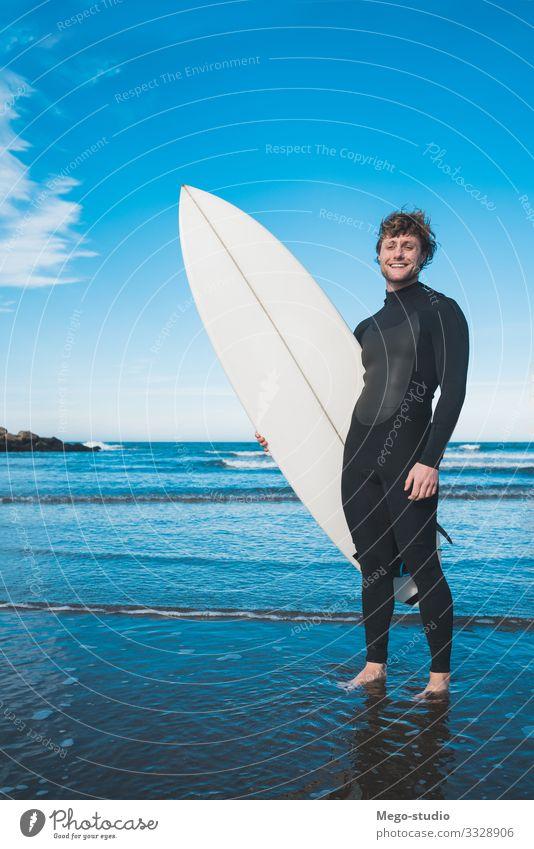 Surfer, der mit seinem Surfbrett im Meer steht. Lifestyle Freude Glück Erholung Freizeit & Hobby Abenteuer Strand Wellen Sport Wassersport Mensch maskulin Mann