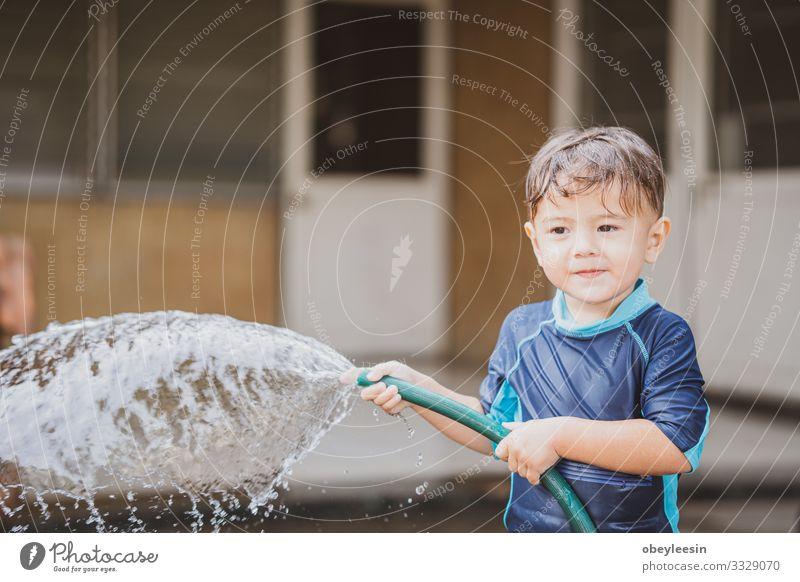 süßer Junge, der draußen mit Wasser in der Natur spielt Freude Glück Erholung Freizeit & Hobby Spielen Sommer Kind Schule lernen Mensch Kindheit Park Wiese