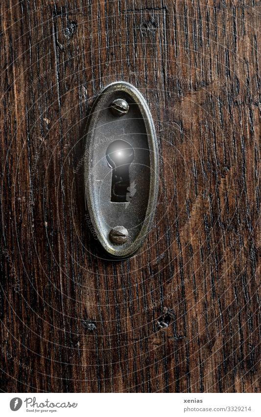Licht im Schlüsselloch weiß Holz braun leuchten Neugier nah Schloss silber Schraube Holzstruktur