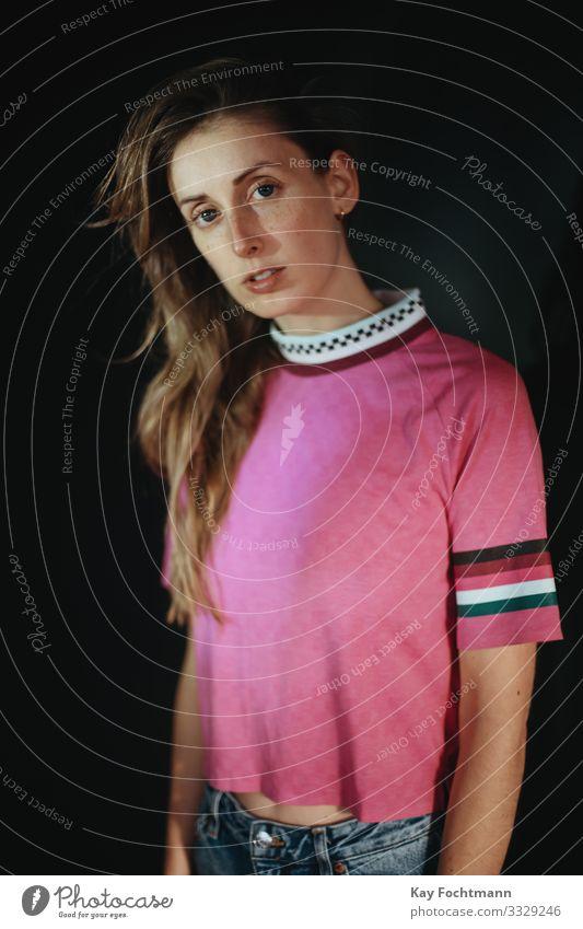 junge Frau in rosa Hemd 20s 30s Erwachsener schöne Frau schwarzer Hintergrund blond braune Haare Freizeitkleidung Kaukasier betroffen Selbstvertrauen Vielfalt