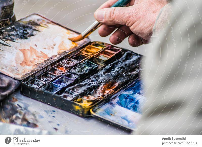 Hand eines Malers vor Palette mit Ölfarben Mensch maskulin Finger Kunst Künstler Arbeit & Erwerbstätigkeit zeichnen ästhetisch blau braun mehrfarbig gelb gold