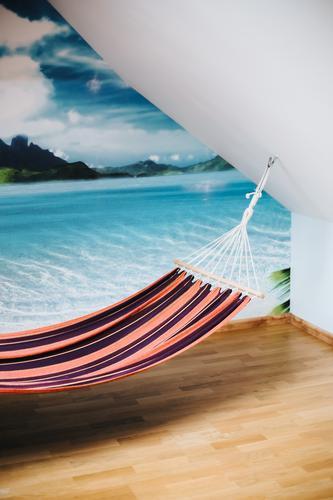 Hängematte in einem Raum mit einem Panoramabild einer tropischen Insel an der Wand Strand Windstille Küste Komfort bequem gemütlich Tag träumen exotisch
