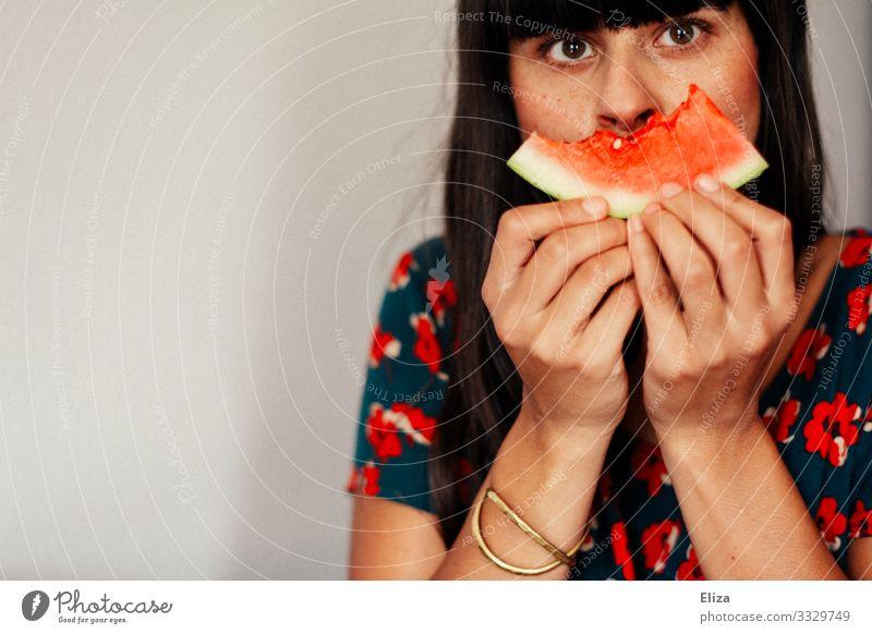 Eine Frau hält sich ein angebissenes Stück Wassermelone vor das Gesicht. Vegane und gesunde Ernährung. Mensch feminin Junge Frau Jugendliche Erwachsene 1
