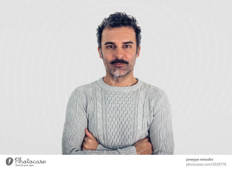 Mann mit Schnurrbart und grauem Pullover, stehend mit verschränkten Armen. Erwachsene attraktiv braun Krebs Freizeitbekleidung Kaukasier selbstbewußt Coolness