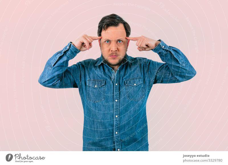 Junger Mann mit Ausdruck von Konzentration. rosa Hintergrund absorbiert Abstraktion erraten betoniert Finger selbstsüchtig Zauberei u. Magie Meditation