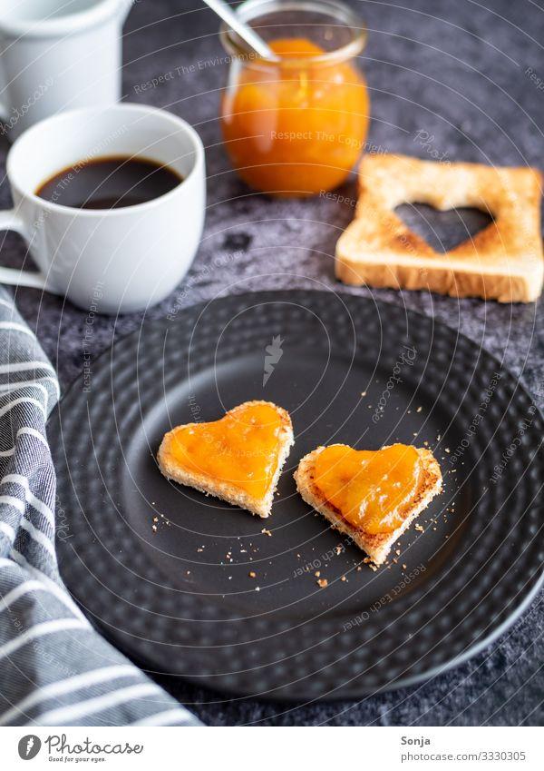 Frühstück mit Toastbrot in Herzform und Aprikosenmarmelade Lebensmittel Brot Marmelade Ernährung Kaffeetrinken Getränk Heißgetränk Teller Tasse Glas Tisch
