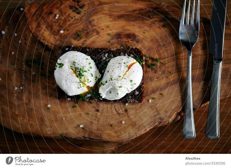 Zwei pochierte Eier auf Schwarzbrot Lebensmittel Brot Körnerbrot Gabel Messer Würzig Ernährung Frühstück Abendessen Bioprodukte Slowfood Deutsche Küche Besteck