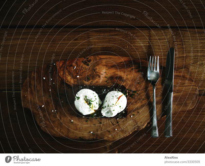 Zwei pochierte Eier auf Schwarzbrot Lebensmittel Teigwaren Backwaren Brot Schneidebrett Besteck Messer Gabel Kräuter & Gewürze Holztisch Ernährung Frühstück