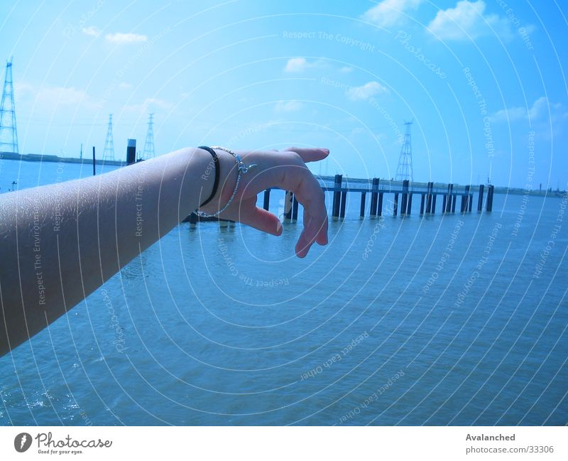 Zeigen des Armes Frau Wasser Meer blau Wolken Armut Finger Schelde