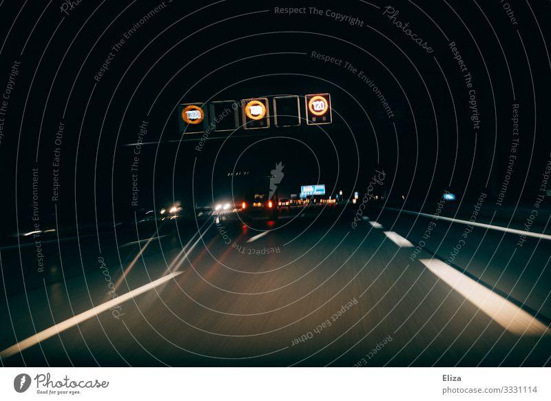 Autobahn mit Autos  und Schildern zur Geschwindigkeitsbegrenzung bei Nacht im dunkeln Verkehr Verkehrsmittel Personenverkehr Straßenverkehr Autofahren PKW