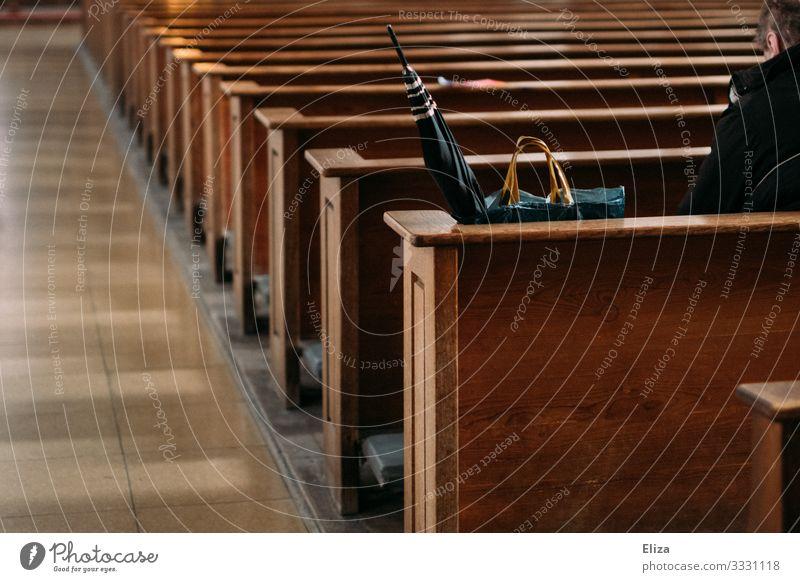 Ein Mann sitzt einsam und alleine neben seinem Regenschirm und Einkaufstasche auf einer Kirchenbank in der Kirche und betet Mensch beten sitzen Bank Einsamkeit