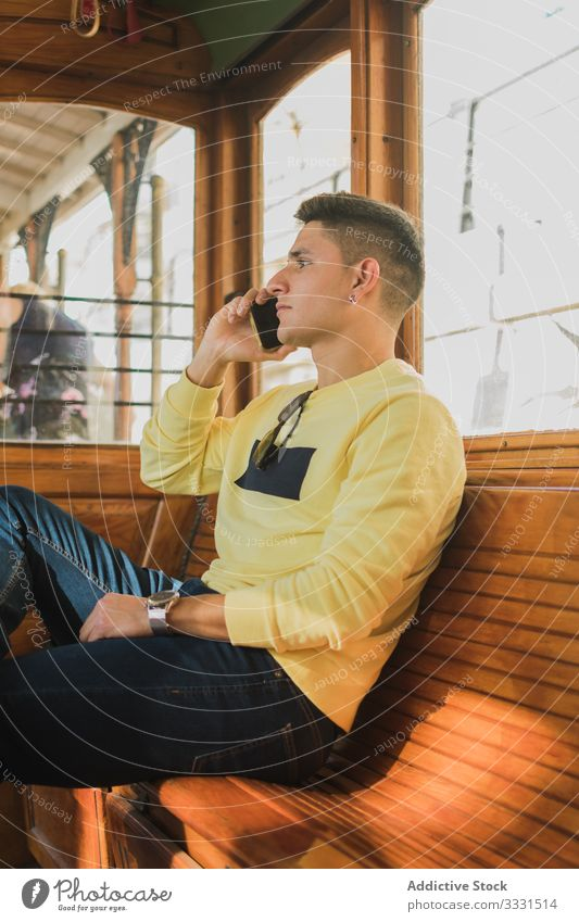 Kerl plaudert am Telefon und fährt im Zug Mann Telefonanruf Smartphone Arbeitsweg benutzend Mobile sprechen Mitfahrgelegenheit Talkrunde Gespräch modern jung