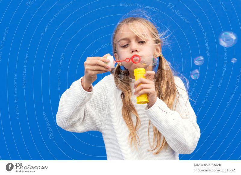 Lustiges Mädchen, das Seifenblasen pustet Blasen spielerisch Kind Spaß Lächeln Lachen lässig wenig Kindheit Hand sorgenfrei Fröhlichkeit schön blasend