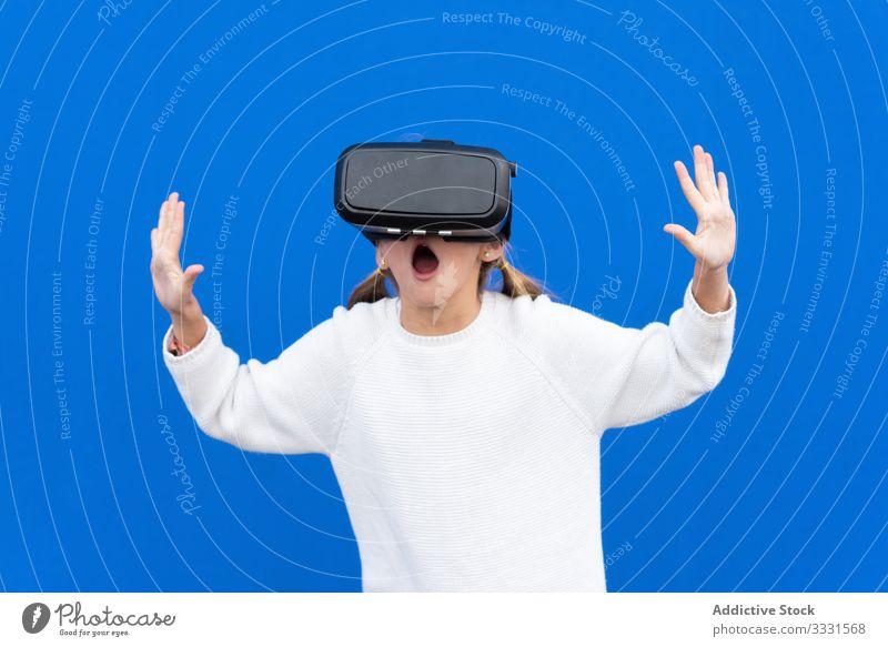 Positives Mädchen spielt VR im Studio Schutzbrille Kind aufgeregt wow erstaunt Spaß Lächeln Lachen lässig Hand sorgenfrei Fröhlichkeit Frau Überraschung