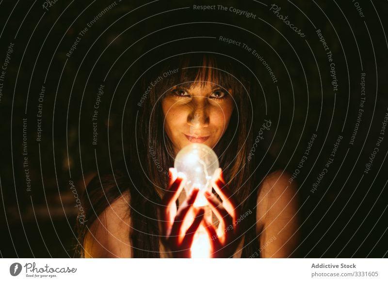 Nachdenkliche Frau mit brennender Glühbirne in der Dunkelheit Brandwunde Model Licht Zauberei u. Magie glühen hell Idee Innovation Energie Lampe Nacht
