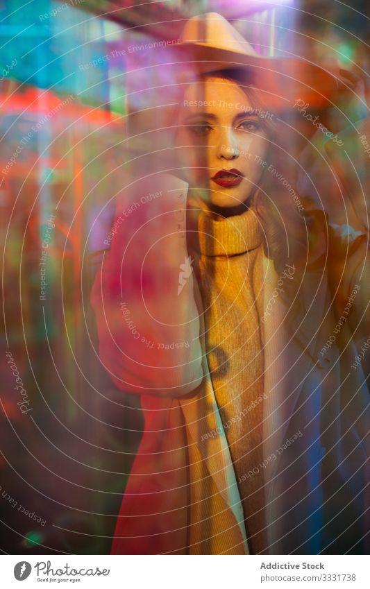Sinnliche junge Frau im Mantel im Licht von Neonschildern neonfarbig Straße Großstadt trendy Verlockung Mode genießen elegant glühen Zeichen farbenfroh modern