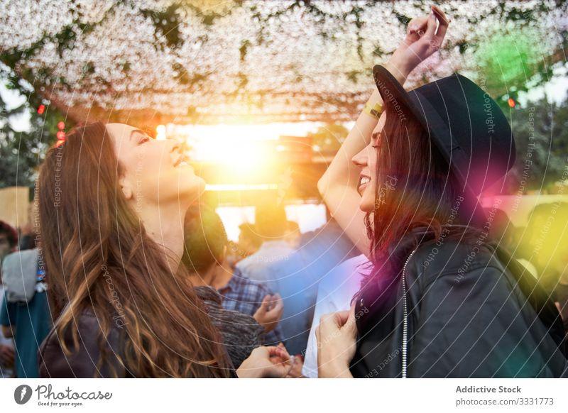 Angenehme Frauen tanzen und haben Spaß bei einer Party im Park Tanzen Stadtfest Erhöhung Handerheben Zwei Personen Leder Jacke Feier Menschengruppe Spaß haben