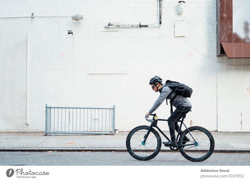 Profi-Radsportler mit Smartphone Mann Radfahrer Fahrrad Großstadt Straße Asphalt Gerät Brille männlich Schutzhelm Sport Lifestyle Bewegung urban Messenger