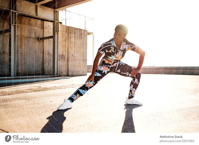 Fitte ethnische Sportlerinnen wärmen sich vor dem Training auf der Straße auf Aufwärmen Dehnung Muskel Hand Physis schlank sportlich Übung Windstille Fitness