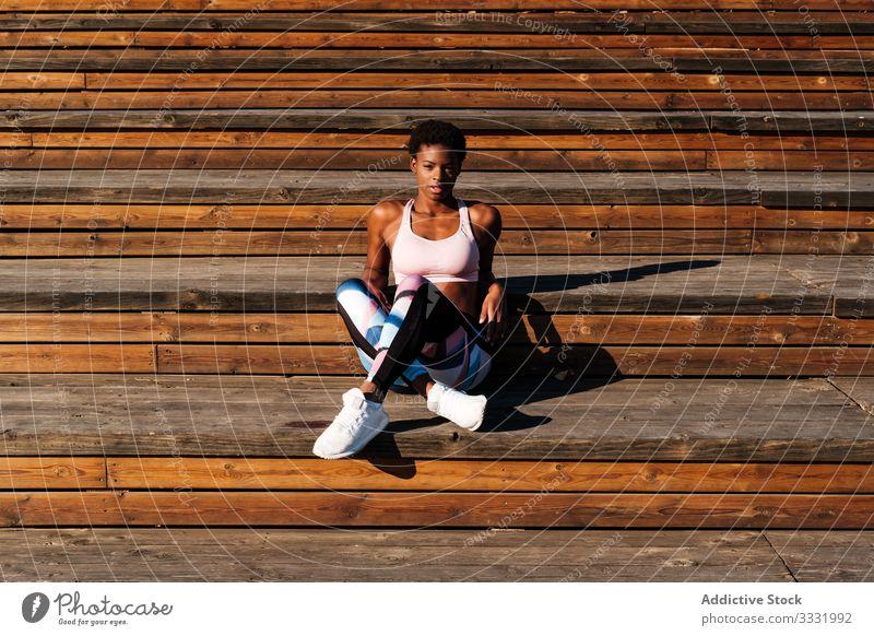 Nachdenklicher tausendjähriger ethnischer Sportler, der sich nach dem Training auf einer Holztreppe im Park entspannt Sportlerin selbstbewusst Treppe Motivation