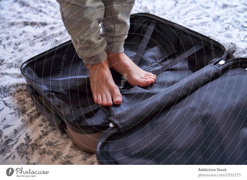 Kornkind im offenen Koffer stehend Kind Schlafzimmer Rudel Bett Barfuß gemütlich heimwärts Feiertag Gepäck Ausflug Urlaub reisen Vorbereitung ruhen