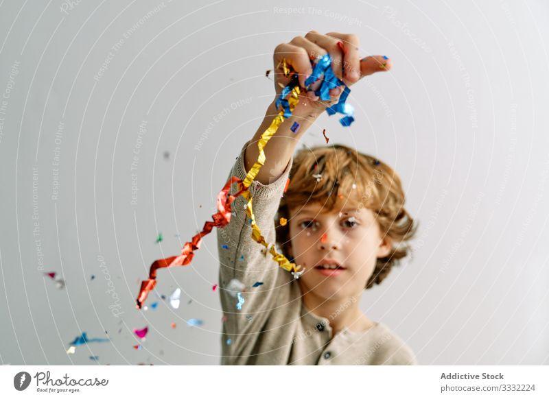 Überglücklicher Junge hat zu Hause Spaß mit Konfetti spielen werfen Sitzen Kind männlich Teenager farbenfroh Lächeln genießen Lachen modern Kindheit Lifestyle