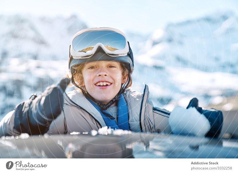 Fröhlicher Junge macht Schneeball im Auto Winter PKW Lächeln rollen Resort sonnig tagsüber Kind Erholung Lifestyle Glück heiter erfreut optimistisch Fahrzeug