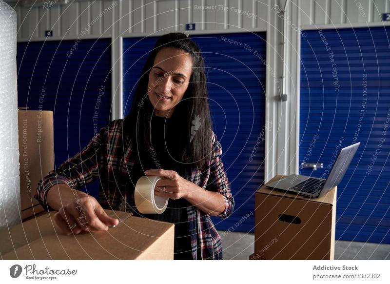 Frau, die Kartons mit Siegelband verschließt Paket Rudel Haushalt Ware Verkehr Versand Transport Kasten Fracht Kauf Beteiligung Umzug transferieren