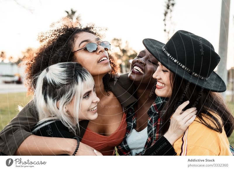 Multiethnische Gruppe von weiblichen Hipsterinnen, die mit jeder einzelnen kuscheln Menschengruppe Frau Kuscheln jung Stil Lächeln Umarmung Porträt Zusammensein