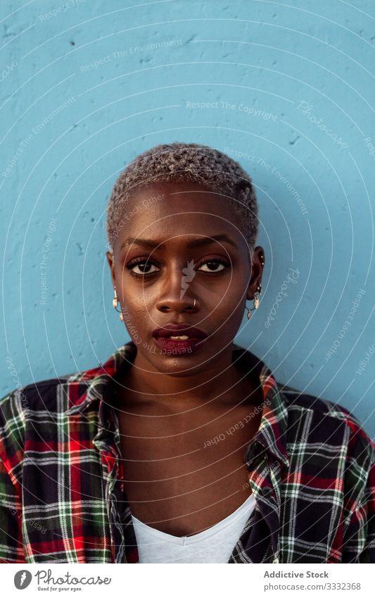 Junge, schwarze, kurzhaarige Frau schaut mit intensivem Blick in die Kamera traurig Porträt Herausforderung Kurze Haare Piercing kariertes Hemd Afroamerikaner
