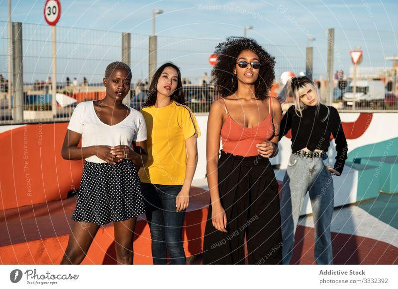 Zuversichtliche junge multiethnische Freundinnen, die sich auf der Straße vergnügen genießen Zeitvertreib Frau Spaß Sitzung Zusammensein Lifestyle Freizeit
